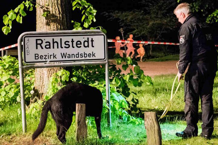 Ein Polizist sucht mit einem Hund einen Tatort im Stadtteil Rahlstedt ab.