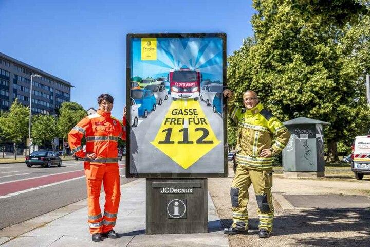 Brandoberinspektorin Jadwiga Richter (39. l) und Feuerwehrsprecher Rainer Jonas (53) mit dem neuen Rettungsgassen-Plakat.