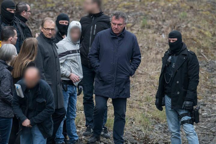 Ali B. bei der Tatortbegehung am 27.03.2019 flankiert von mehreren maskierten Polizeibeamten.