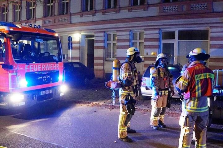 Feuerwehrmänner stehen mit Atemschutzmasken vor dem Haus.