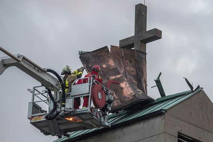 Von einem Hubsteiger aus versuchen Feuerwehrmänner, das Blechdach eines Kirchturms im Stadtteil Gallus zu sichern, welches sich losgerissen hatte.