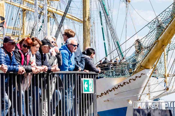 Besucher stehen am letzten Tag des 830. Hamburger Hafengeburtstags an einem Geländer bei den Landungsbrücken vor dem russischen Großsegler Mir.