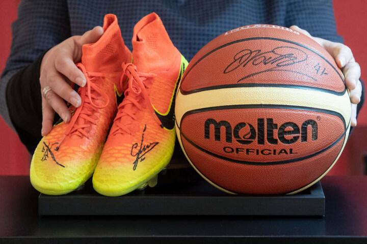 Mitarbeiterin des Auktionshauses Eppli präsentiert die handsignierten Schuhe von Mario Götze und den Basketball von Dirk Nowitzki.