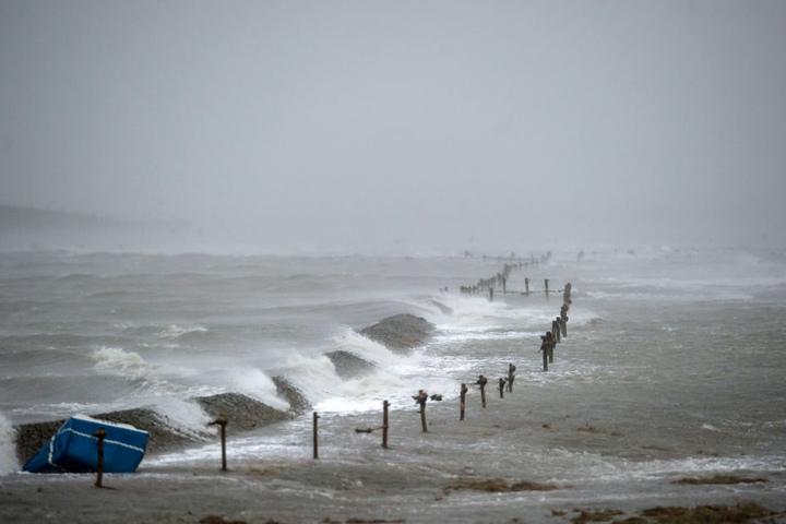Ein Deich der nordfriesischen Hallig Langeneß wird während eines Orkans überspült. (Archivbild)