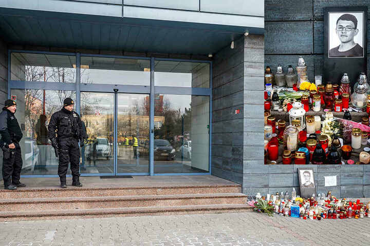 Vor dem Eingang zum Bürogebäude des Nachrichtenportals «aktuality.sk» haben Menschen Kerzen und Blumen im Gedenken an die beiden Ermordeten niedergelt. Das Gebäude wird von Polizisten bewacht.