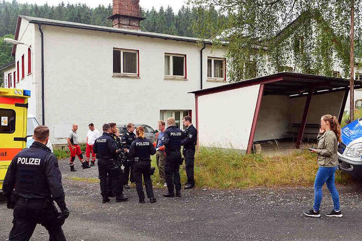Polizisten und Sanitäter stehen vor dem früheren Firmengebäude eines ehemaligen glasschmuckverarbeitenden Betriebes in Haselbach (Thüringen).