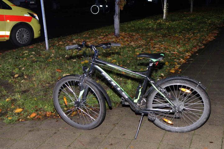 Das Fahrrad des Jungen steht auf einem Gehweg.