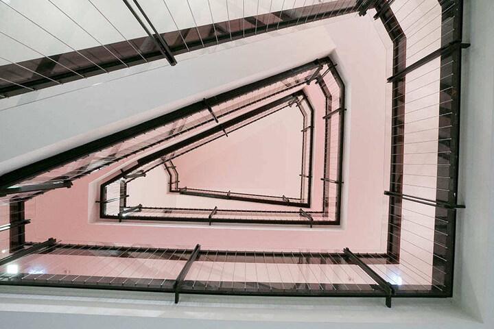 Ein Blick ins Treppenhaus: Das ursprüngliche Geländer wird durch erhöhte  Glasscheiben gesichert.