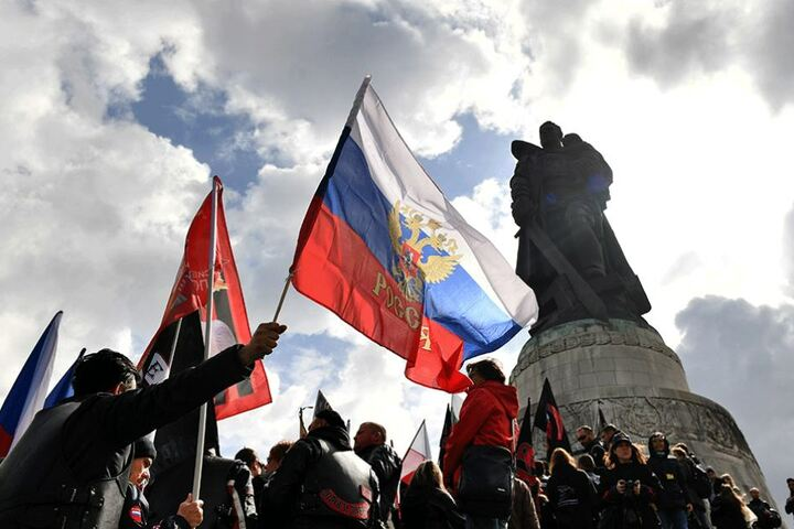 """Die """"Nachtwölfe"""" schwenken russische Fahnen vor dem Ehrenmal."""