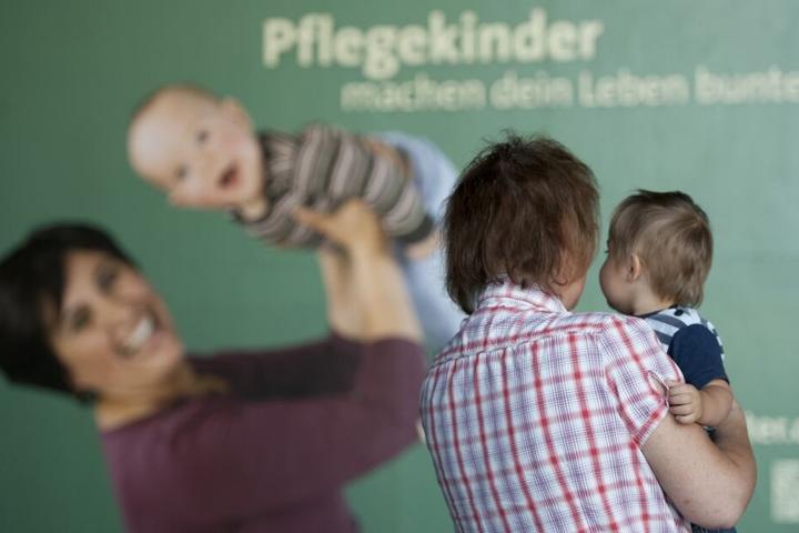 """Eine Frau steht mit einem Kind im Arm vor einem Plakat mit der Aufschrift """"Pflegekinder machen dein Leben bunter""""."""