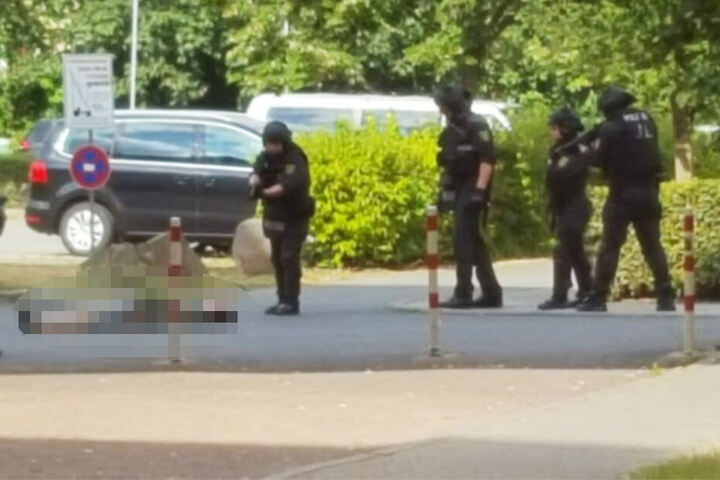 Ein Polizist beugt sich über eine am Boden liegende Person.