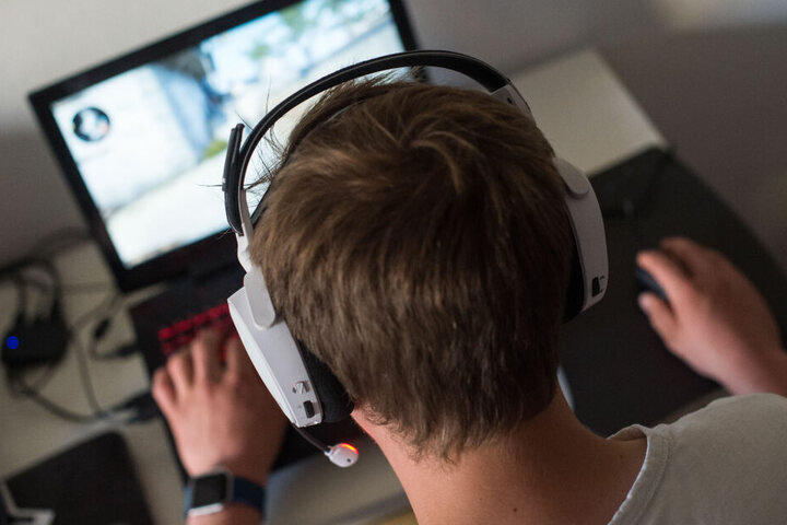 Ein Junge sitzt mit einem Headset vor einem Laptop und spielt ein Online-Computerspiel. (Symbolbild)