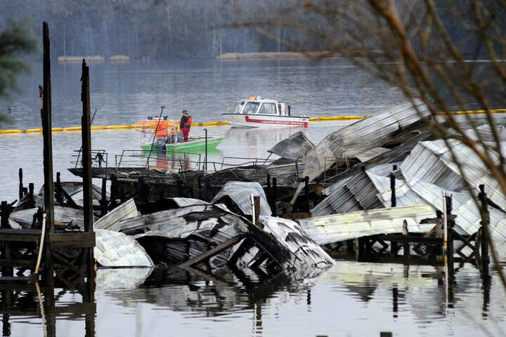 Ein Boot patrouilliert in der Nähe der verkohlten Überreste des bei einem Brand zerstörten Docks und mehrerer Hausboote.