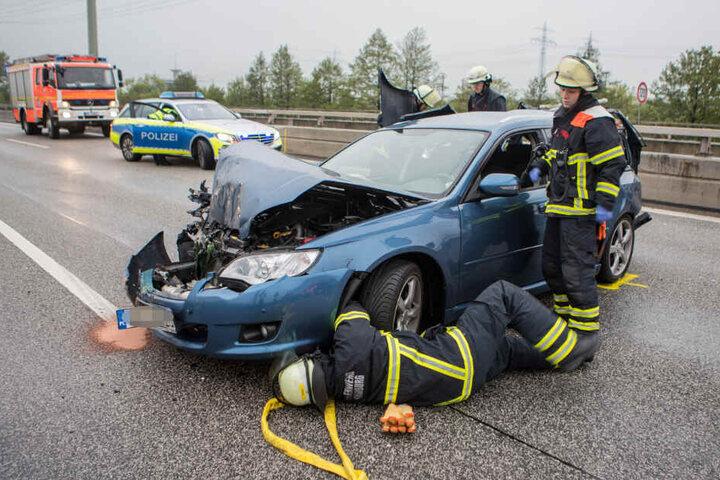 Feuerwehrkräfte untersuchen eines der beteiligten Unfall-Fahrzeuge.