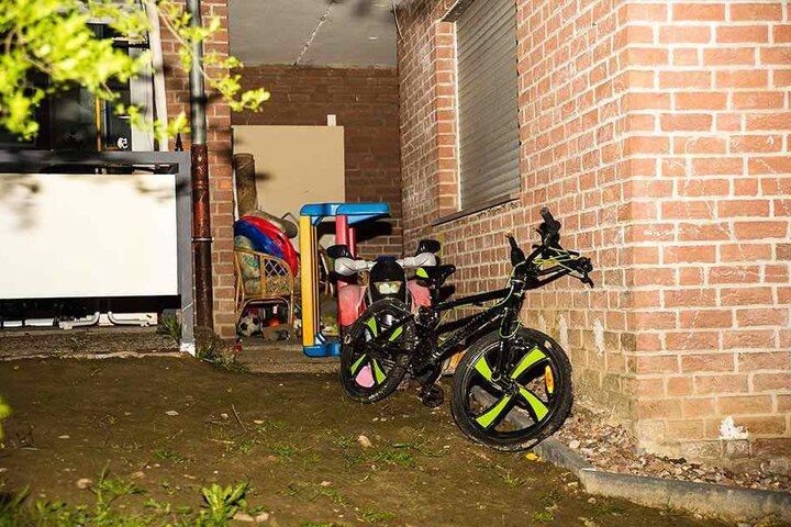 Unter dem Fenster stehen das Fahrrad des toten Jungen und anderes Spielzeug.