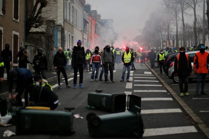 """Teilnehmer bei einer Demonstration der """"Gelbwesten"""" stehen in Bourges (Frankreich) auf der Straße und zünden rote Fackeln an."""
