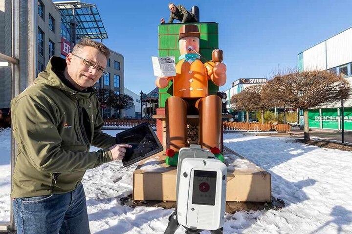 Ingo Eppert (47) und Detlef Wuttke (57, hinten) können die Größe des Riesen durch einen Laserscanner ermitteln.