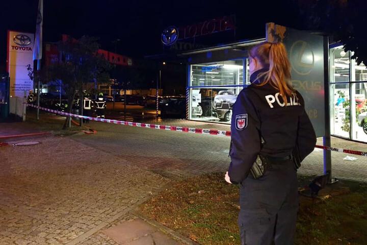 Eine Polizistin steht vor dem Autohaus.