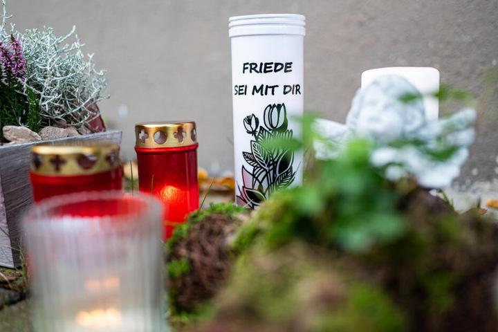Vor dem Haus, wo der Dreijährige getötet wurde, legten Menschen Blumen und Kerzen hin.