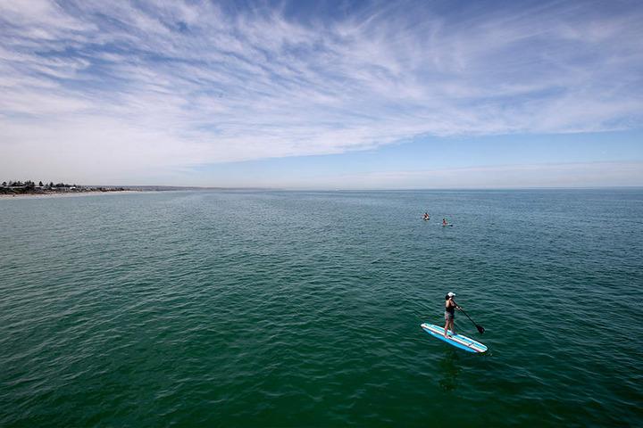 Ein Stehpaddler war am Donnerstag auf dem Wasser unterwegs am Henley Beach in Adelaide.