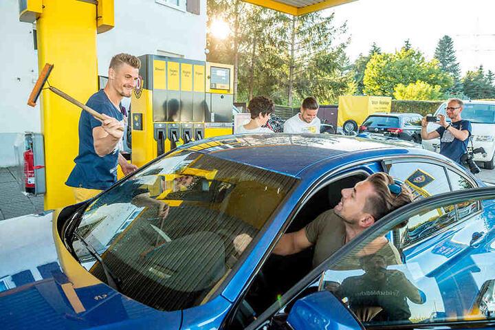 Während Patrick Wiegers das Auto vorfährt, wischt Stefan Kutschke ihm die Scheibe sauber.
