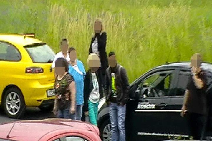 """Der """"Verletzte"""" steht neben dem Auto, während der Fahrer (re.) telefoniert, um Hilfe zu rufen."""