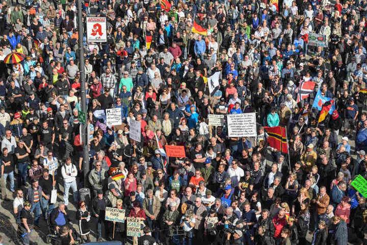 Viele Demonstranten stehen mit Transparenten und Fahnen auf einem Platz vor der Stadthalle von Cottbus und protestiert gegen Zuwanderung und die Asyl-Politik der Bundesregierung.