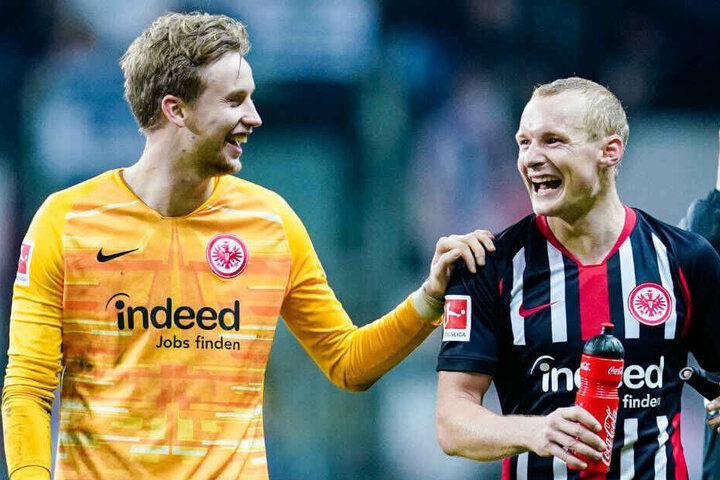 Frederik Rönnow (li.) freut sich mit Sebastian Rode (re.) über den 3:0-Sieg von Eintracht Frankfurt über Bayer Leverkusen.