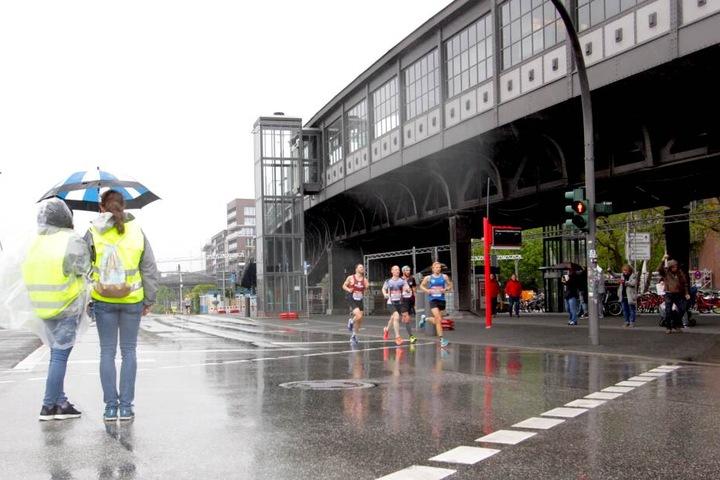Zwei Helferinnen beaufsichtigen, mit Regenschirmen ausgestattet, die Marathonstrecke auf der Höhe des U-Bahnhofs Baumwall.