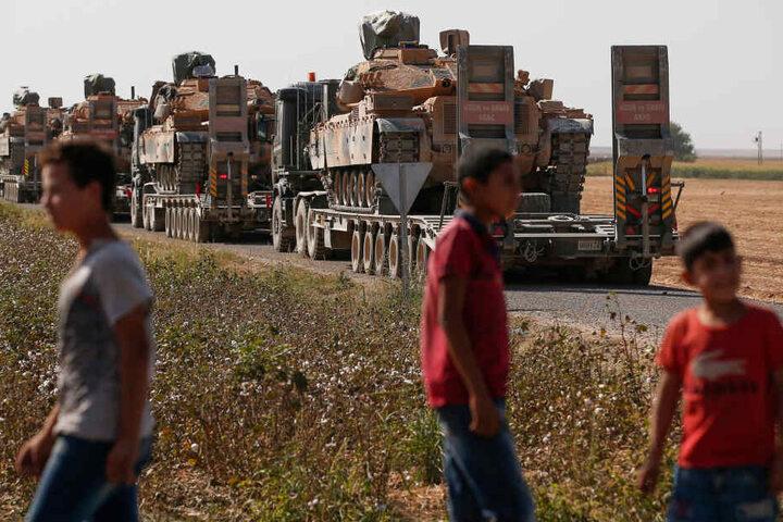Anwohner stehen vor einem Lastwagen-Konvoi türkischer Streitkräfte, in dem Panzer transportiert werden. Die Türkei hatte am 09.10.2019 eine lang geplante Offensive gegen Kurdenmilizen begonnen, die auf syrischer Seite der Grenze ein großes Gebiet kontroll
