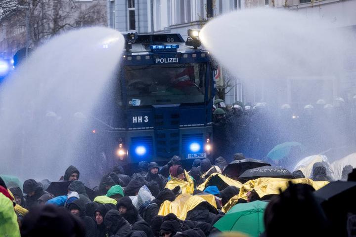Die Demonstranten versuchen, sich bei der Kälte gegen das Wasser zu schützen.