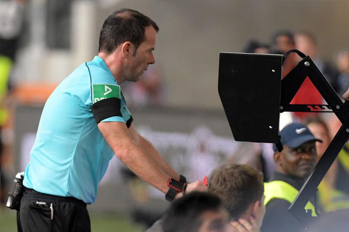 Schiedsrichter Marco Fritz schaut sich eine Szene auf dem Bildschirm an der Seitenlinie noch einmal an.