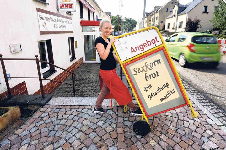 Sexkornbrot im Angebot! Franziska Müller schiebt einen Werbe-Aufsteller vor  die Tür der Bäckerei.