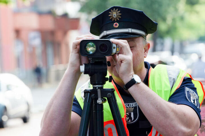 Ein Polizeibeamter misst mit einer Radarpistole die Geschwindigkeit der Fahrzeuge. (Archivbild)
