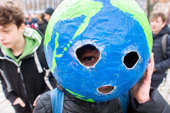 """Ein Schüler trägt auf der """"Fridays for Future""""-Kundgebung eine Weltkugel aus Pappmache auf dem Kopf."""