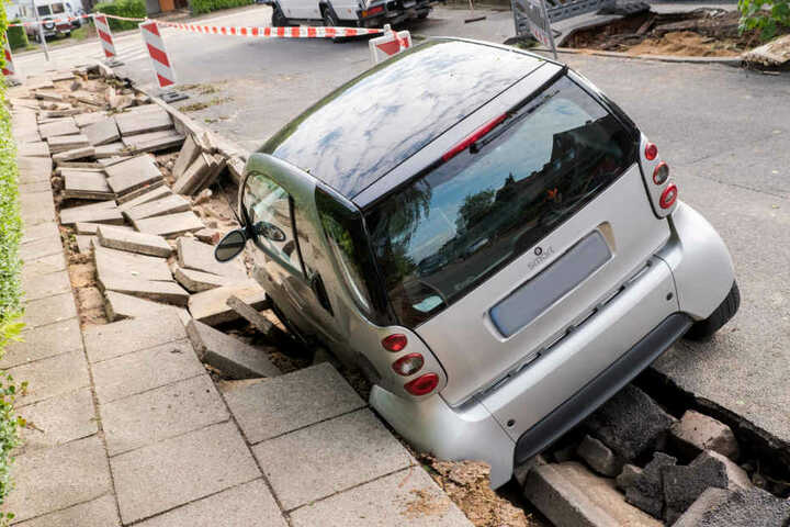 Nach der Überflutung steckt ein Auto in der abgesackten Straße fest.