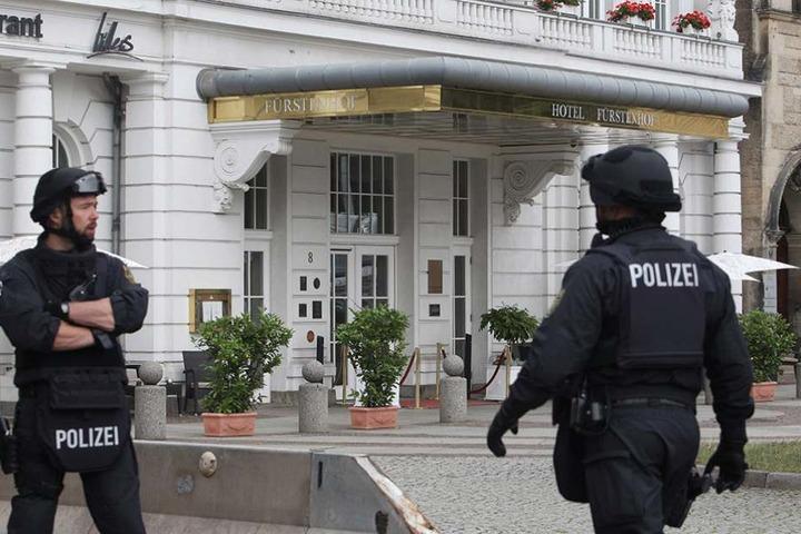 """Zwei Polizisten stehen in voller Ausrüstung vor dem Hotel """"Fürstenhof"""" in Leipzig."""