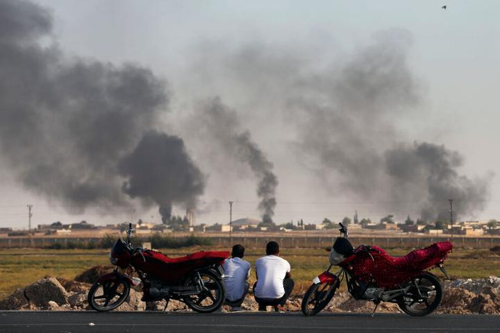 Akcakale in der Türkei: Zwei Männer schauen auf den Militäreinsatz in Nordsyrien.