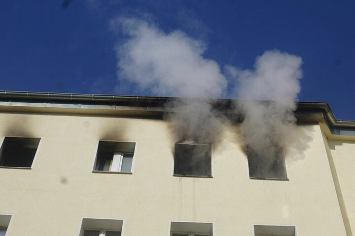 Aus einer Wohnung im Dachgeschoss tritt dichter Rauch aus.
