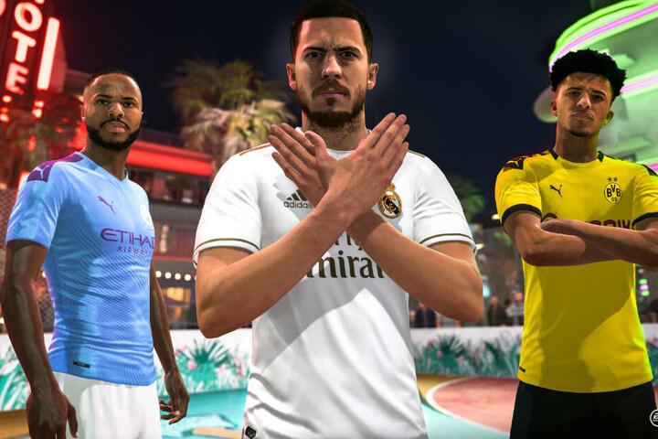 """Manchester Citys Raheem Sterling (links im Bild) und Dortmunds Jadon Sancho (rechts im Bild) stehen zusammen mit """"FIFA 20""""-Cover-Star Eden Hazard von Real Madrid auf einem VOLTA-Streetplatz."""