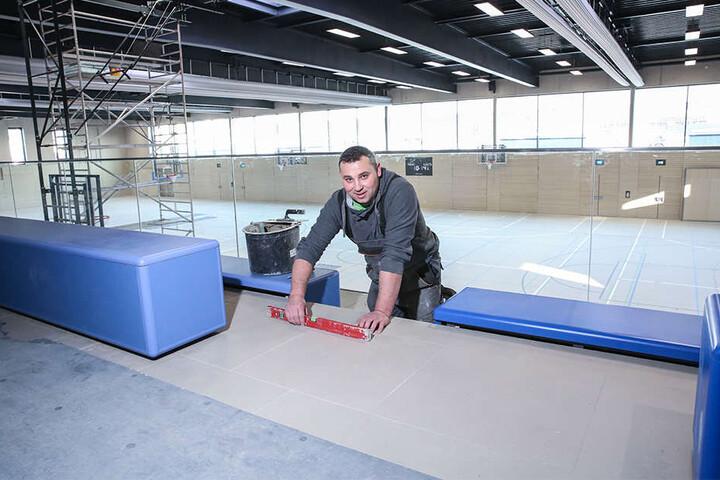Letzter Schliff: Sebastian Nikiel (39) verlegt Fliesen in der Sporthalle.