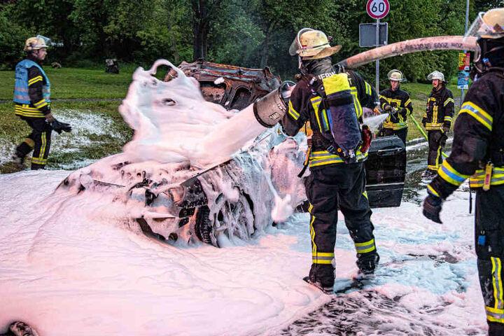 Feuerwehrleute löschen das Auto.
