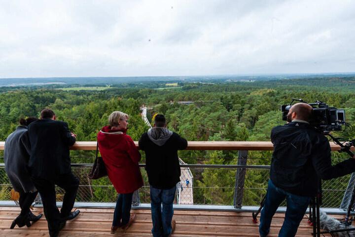 Gäste blicken vom Aussichtsturm des Baumwipfelpfades auf die Landschaft.