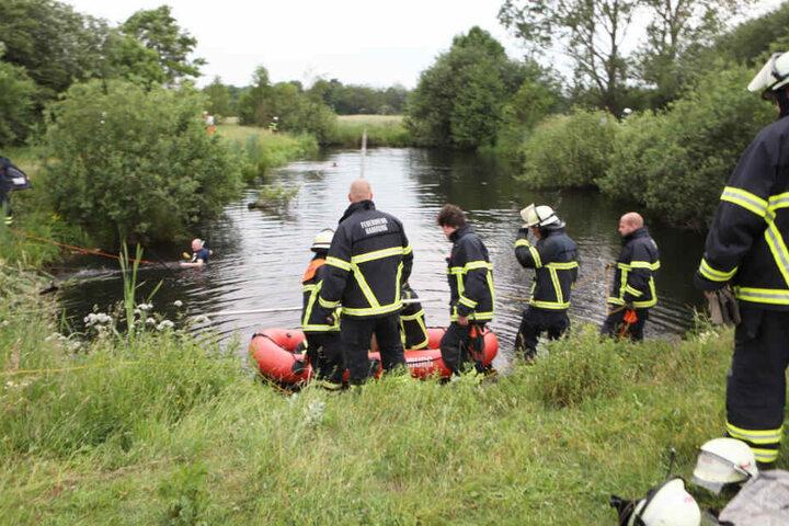 Feuerwehrleute suchen nach dem Jungen im Wasser.