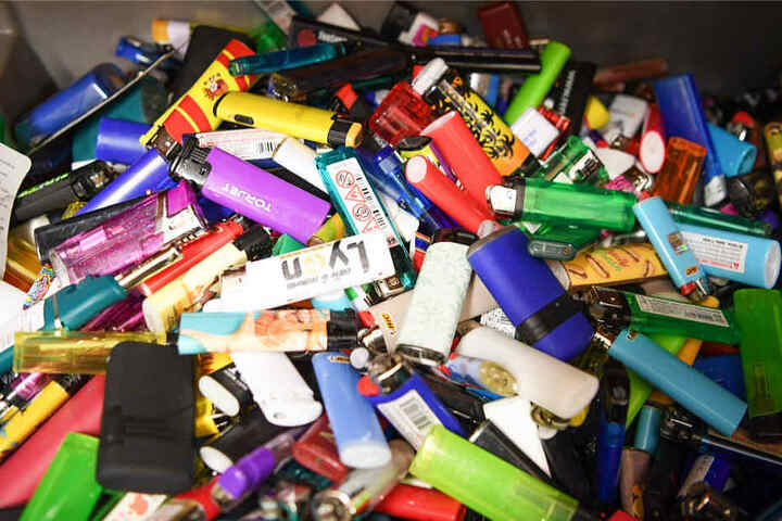 Zahlreiche Einwegfeuerzeuge werden im Fundbüro am Frankfurter Flughafen in einer Kiste gelagert.