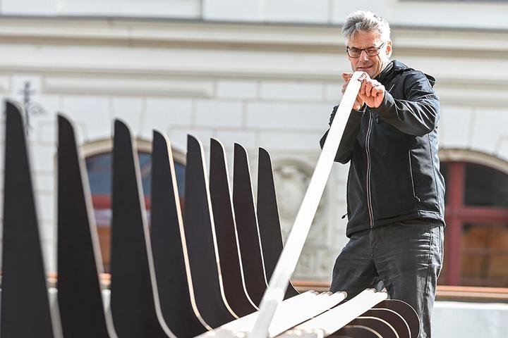 Technik-Direktor Mario Radicke (59) ordnet fachgerecht die Latten für die XXL-Holzbank.