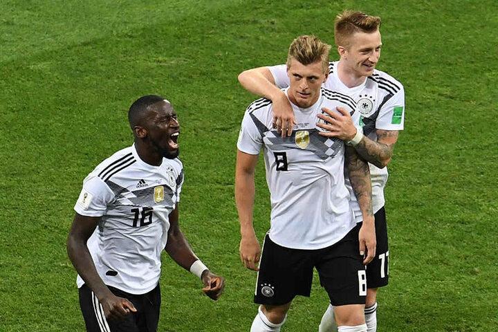 Antonio Rüdiger (l.) brüllt seine Freude heraus und Marco Reus (r.) herzt Torschützen Toni Kroos (M.), der Deutschland in letzter Sekunde zum 2:1-Sieg schoss.