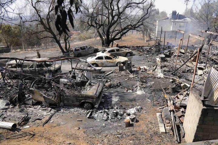 Verkohlte Autos und Gebäude, die von einem Buschfeuer zerstört worden sind.