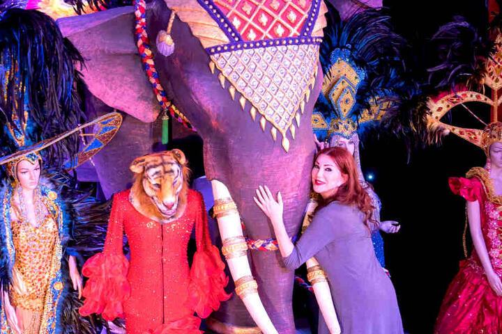 Zum Abschied streichelt Zora ihrem  Elefanten (2500 Euro) den Rüssel. Das rote Kleid kostet 1500 Euro, die blauen  Kostüme daneben 800 bis 1000 Euro.