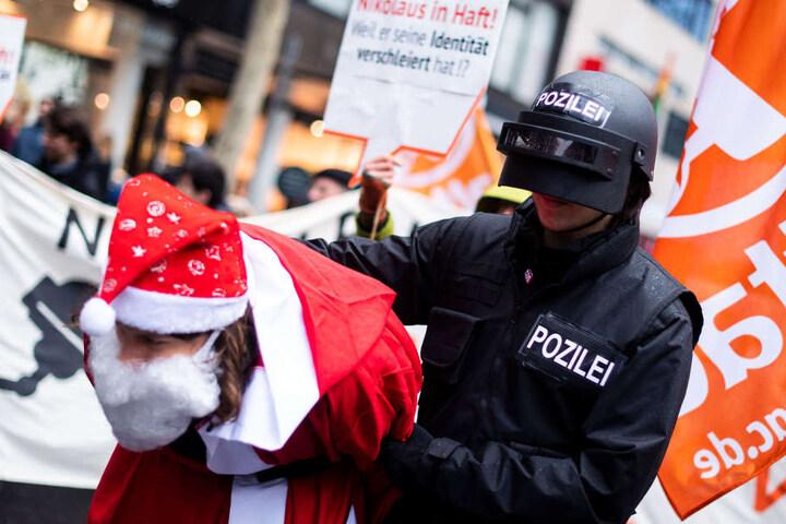 Ein als Polizist verkleideter Teilnehmer der Demo verhaftete den Weihnachtsmann.